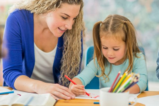 teacher helping child draw with colored pencils